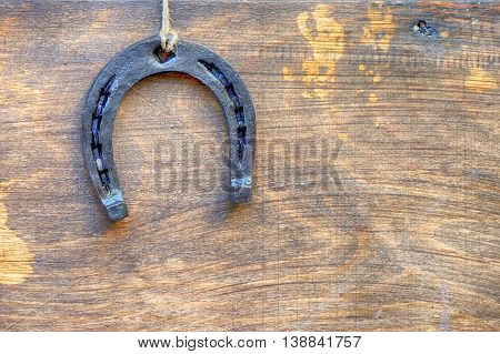New metal horseshoe on old retro vintage aged wooden background Empty space for inscription or object Symbol of lucky