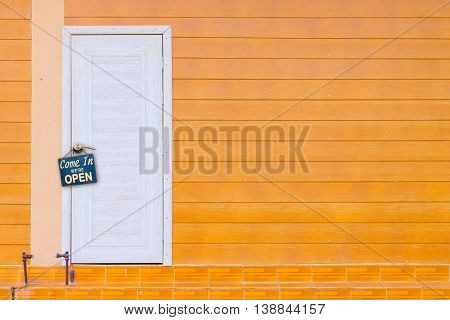 white wooden door and the orange wall with old rusty metalplate with word Come In We're Open haning on a knob copyspace.