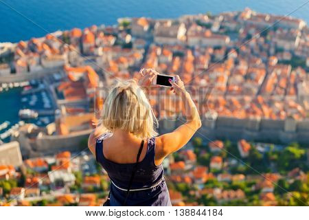 Female traveller make a panoramic photo of the old city of Dubrovnik from the mountain to her phone.