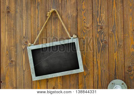 blank space on black chalk board with rope on wooden door of a coffee shop
