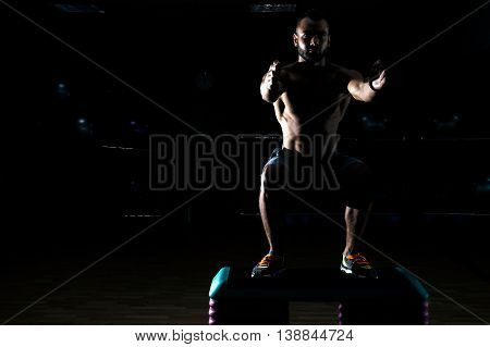 Young Sportsman Crouches Before Workout In Gym