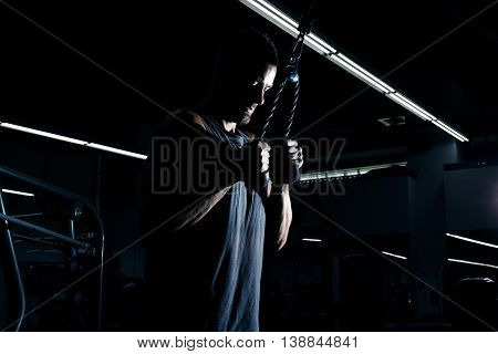 Muscular Young Man Bodybuilder Doing Heavy Weight Exercise For Triceps On Cable Machine