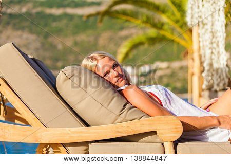 Amazing sensual seductive woman lying on deckchair, enjoying summer holidays near the pool against the background of palm trees.
