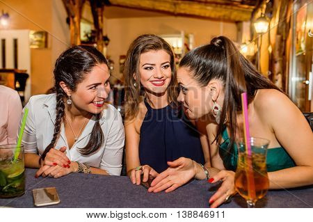 Young beautiful women with cocktails in bar or club talking, having fun