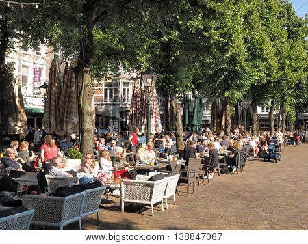 The Hague Netherlands - July 8 2016: Patrons frequenting cafés and restaurants at the historic city square called The Plain in The Hague in the afternoon on a sunny spring day.