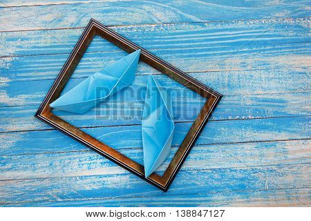 Blue paper boats and photo frame. Travel style