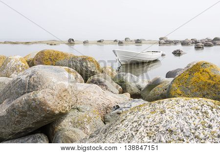 White boat in a shore behind large rocks fog in the background