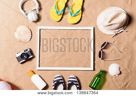Summer vacation composition with picture frame, pair of yellow flip flop sandals, hat, sunglasses, sun cream and other stuff on a beach. Sand background, studio shot, flat lay. Copy space.