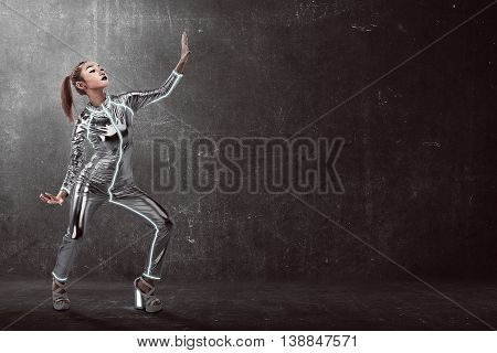 Woman Wearing Latex Jumpsuit Posing Over Grunge Background