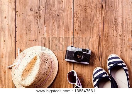 Summer vacation composition. Hat, vintage camera, sunglasses and striped espandrilles shoes on wooden background, studio shot, flat lay. Copy space.