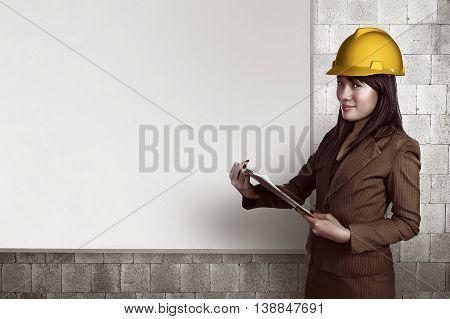 Woman Wearing Helmet Holding Clipboard