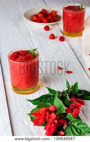 glass of berry smoothie of strawberries and raspberries and flowers