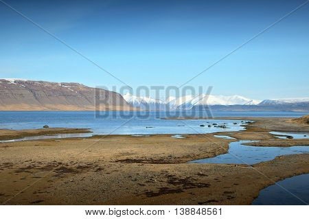 The clear blue sky reflects in the still waters of a Fjord in north western Iceland, the pristine white mountains of the Hornstrandir peninsula lay low on the horizon.