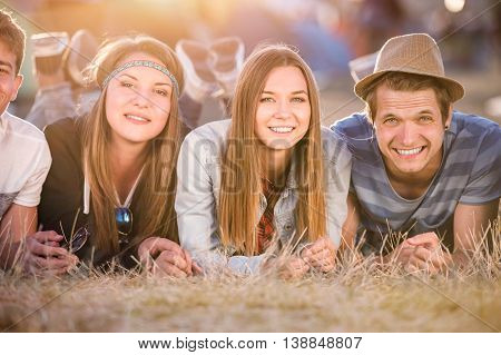 Group of teenage boys and girls at summer music festival, lying on the ground in front of tents
