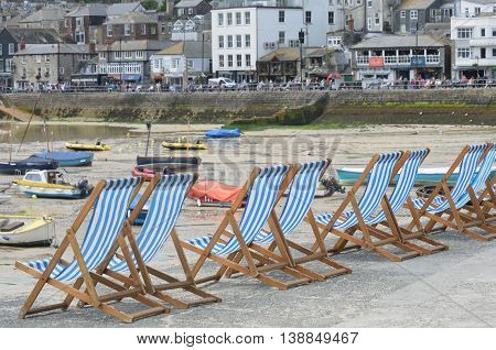 St Ives Cornwall United Kingdom - July 03 2016: Line of deckchairs with town in the background