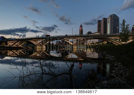Main Street bridge at dusk with cloudy vibrant sky and smooth reflection in the river.