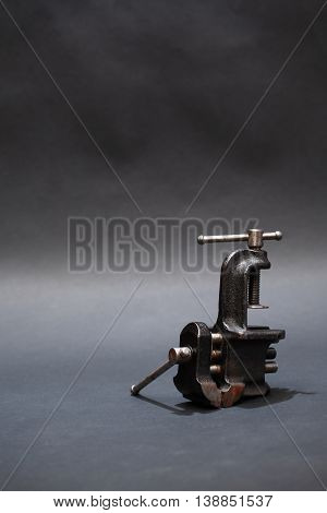 Old metal vise on dark background with free space for text