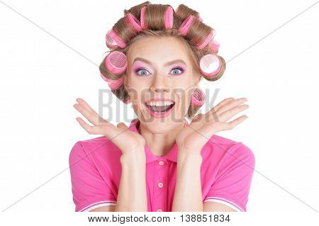 portrait of Beautiful surprised woman in hair curlers in studio