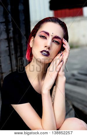 Attractive young woman with colorful makeup, red hairstyle, expressive eyes and piercing on forehead