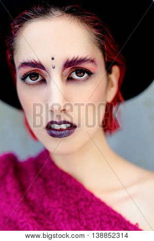 Attractive young woman with colorful makeup, red hairstyle and piercing on forehead in black rounded hat