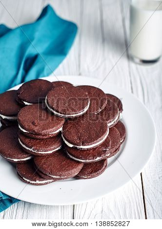 Sandwich chocolate or cacao cookies filled with butter cream on wood background with milk on back.