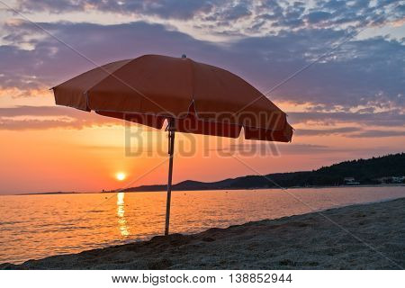 Sandy beach with one orange sunshade at sunset in Sithonia, Greece