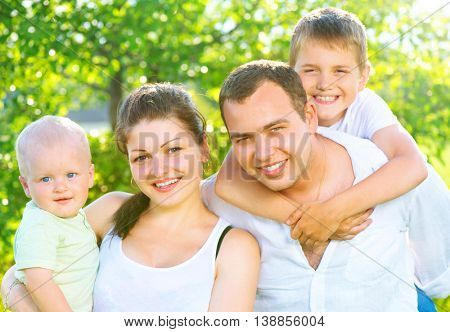 Happy joyful young family portrait. Father, mother and little sons having fun outdoors in orchard garden, playing together in summer park. Mom, Dad, kids laughing and hugging, enjoying nature outside