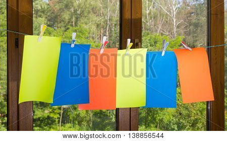 Blank sheets of colored paper fixed a plastic clothespins with colored inserts on clothesline on a blurred background of the window and the trees