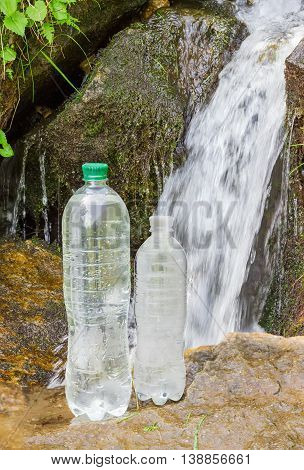 Two plastic bottles of drinking water different sizes on wet stone on the background of a small waterfall on the mountain stream
