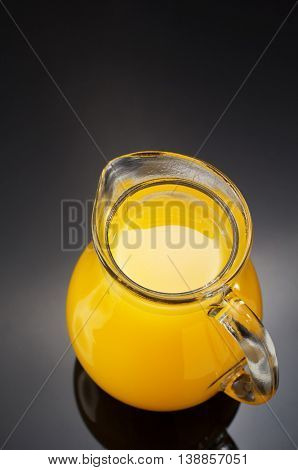 glass pitcher and orange juice on black background