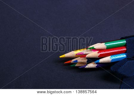 Set of colored pencils wrapped in a blue ribbon on black background. Back to school.