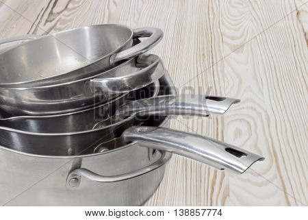 Fragment of a stack of stainless steel stock pots and other cooking utensil with various handles on the background of a wooden surface