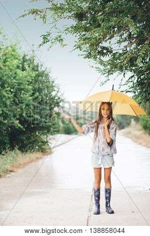 Preteen child wearing rubber boots and holding umbrella walking in the rain
