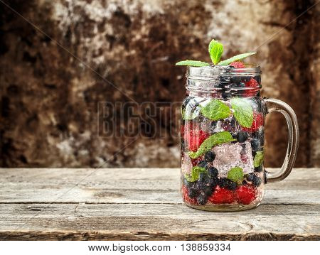 Detox drink with fresh berries, mint and ice in glass jars on wooden background