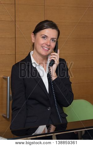 Cheerful receptionist answering at the telephone in hotel