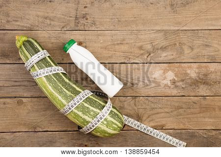 Marrow Squash, Measure Tape And Bottle Of Water On Brown Wooden Table