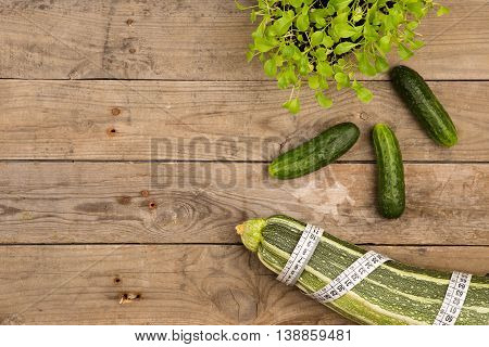 Marrow Squash, Measure Tape And Cucumbers On Brown Wooden Table