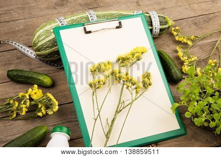 Marrow Squash, Measure Tape, Blank Clipboard, Bottle Of Water, Yellow Flowers And Cucumbers On Brown