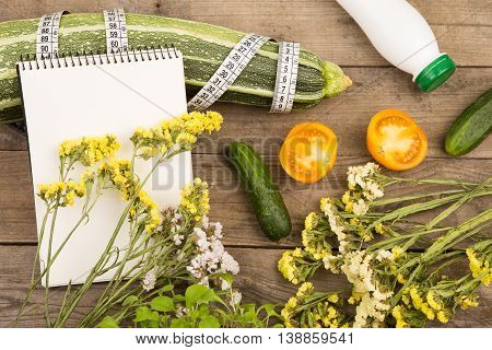 Marrow Squash, Measure Tape, Blank Notepad, Bottle Of Water, Flowers, Tomatoes And Cucumbers On Brow