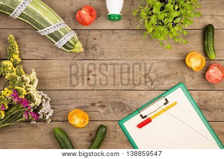 Marrow Squash, Measure Tape, Blank Clipboard, Bottle Of Water, Flowers, Tomatoes And Cucumbers On Br