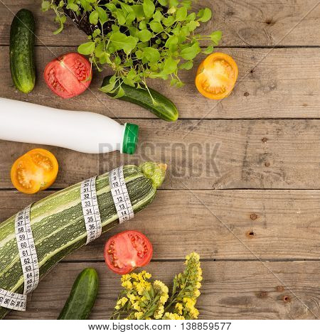 Marrow Squash, Measure Tape, Bottle Of Water, Flowers, Tomatoes And Cucumbers On Brown Wooden Table