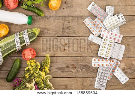 The Choice Between A Healthy Lifestyle And Medications, Vegetables Or Pills On Brown Wooden Desk