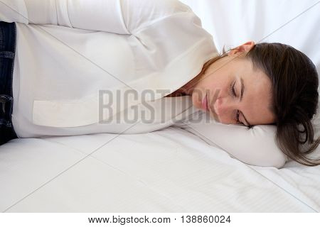 Sad depressed woman lying on the bed