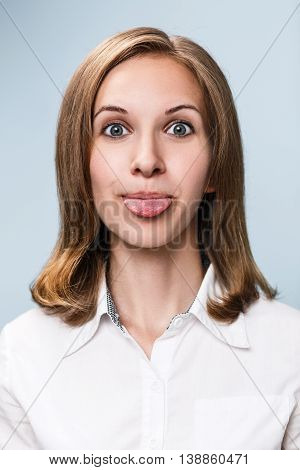 Young funny woman showing grimace with tongue over blue background