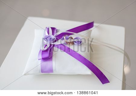 Golden wedding rings on decorated little pillow with purple ribbons
