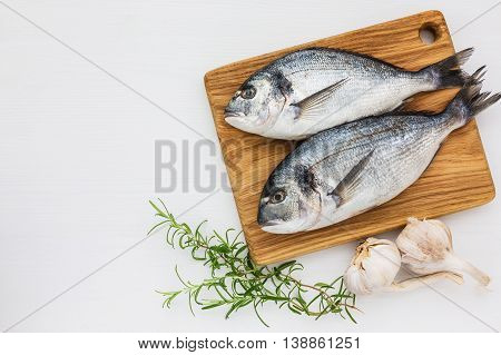 Fresh Dorado Fish On Wooden Cutting Board With Garlic And Rosemary On White Table. Top View, Copy Sp