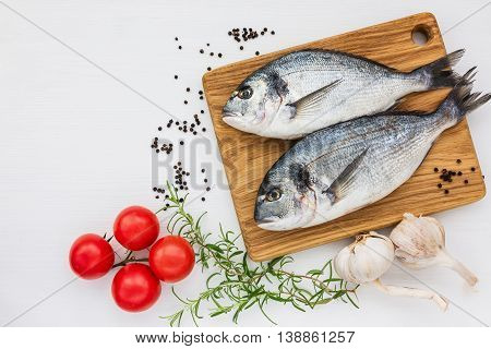 Fresh Dorado Fish On Wooden Cutting Board With Garlic, Rosemary And Tomatoes On White Table. Top Vie