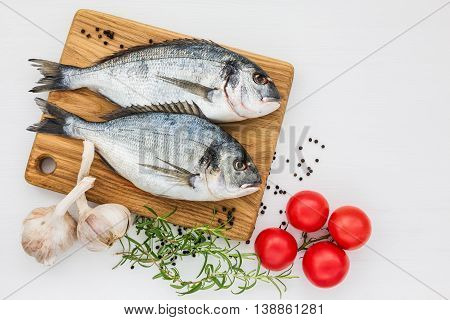 Fresh Dorado Fish On Wooden Cutting Board With Garlic And Tomatoes On White Table. Top View, Copy Sp