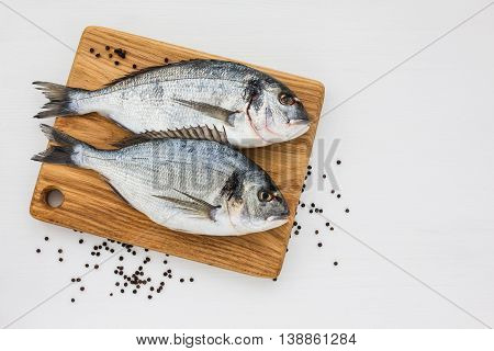Two Fresh Dorado Fish On Wooden Cutting Board On White Table. Top View, Copy Space.