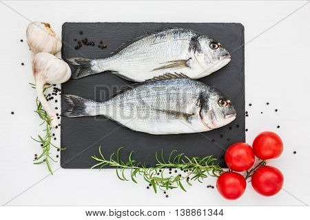 Fresh Dorado Fish On Slate Cutting Board, Rosemary, Garlic And Tomatoes On White Table. Top View, Co